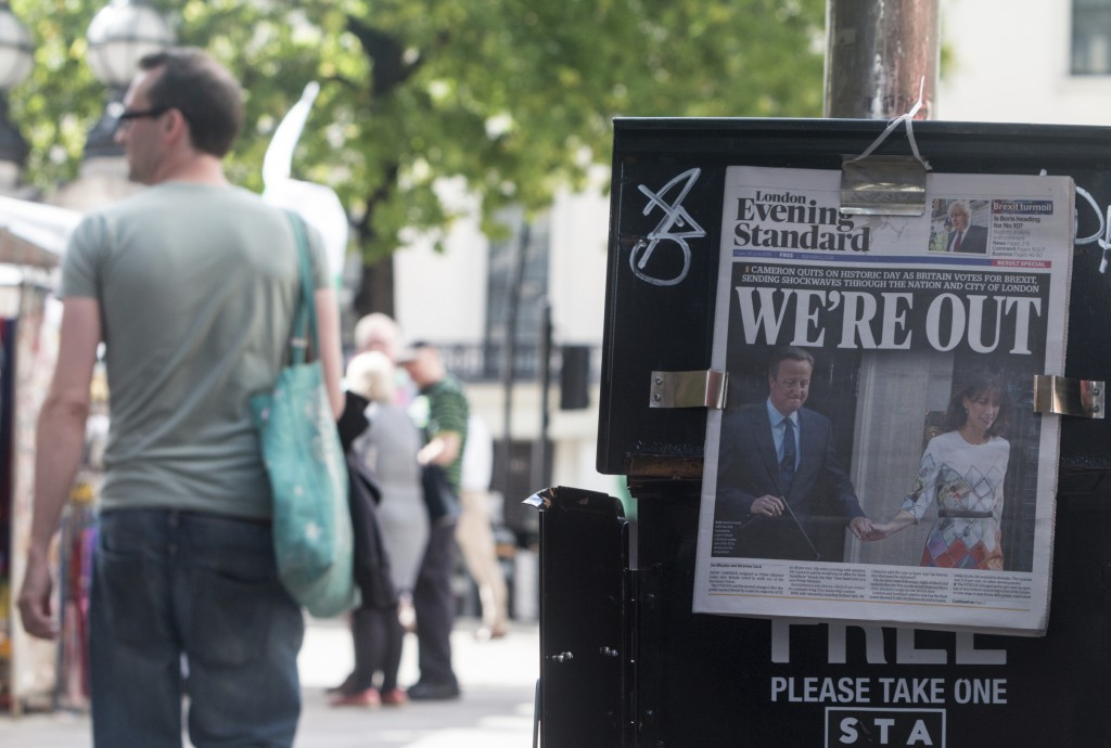 London, UK - June 24, 2016: People walk past a newspaper banner in which The Evening Standard in London reflects the news that the UK has voted to leave the EU, and its PM David Cameron has resigned. These papers were seen on the streets of London, near Charing Cross.