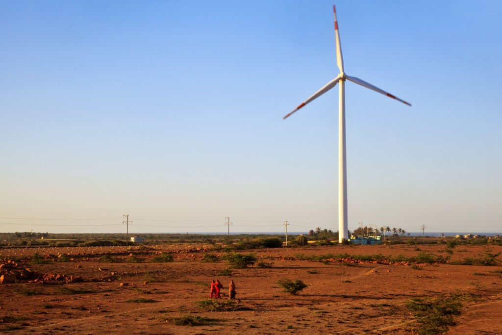 Gujarat, India - February 28, 2013: A group of Indian ladies walk across a barren field with a windmill generator an d farmhouse in the background under a clear blue sky. Shot location 4km outskirts of Dwarka a religious Hindu towb