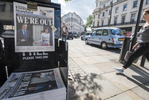 London, UK - June 24, 2016: People walk past a newspaper banner in which The Evening Standard in London reflects the news that the UK has voted to leave the EU, and its PM David Cameron has resigned. These papers were seen on the streets of London, near The Strand.