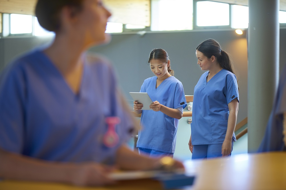 Two young female nurses wearing blue scrubs and holding medical records are reading the medical notes of a patient. they are walking on a busy corridor of a modern hospital . More nurses are defocussed in the foreground.
