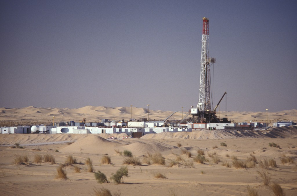 An Oil & Gas Industry drilling rig is surrounded by portable housing units and equipment in support of the drilling of an exploration oil well in the Sahara Desert, Algeria, Africa. Sand dunes, sparce vegetation and a clear afternoon sky make up background and foreground.
