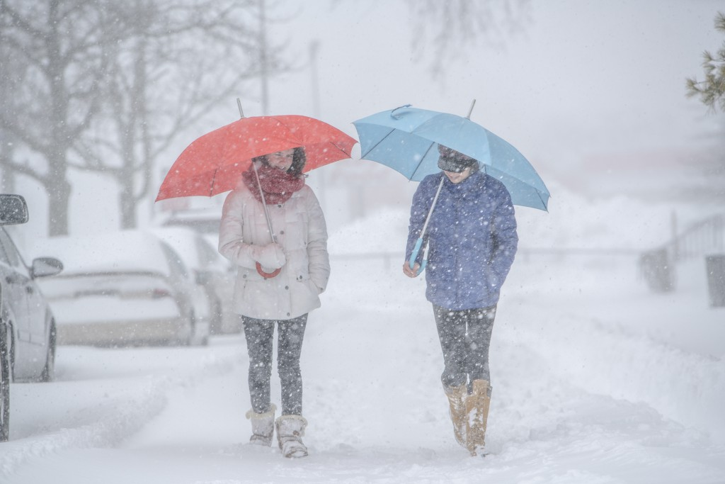 Two teenager girls with umbrellas under snowfall at the street in Queens Village, New York City, NY, during the snowstorm Jonas