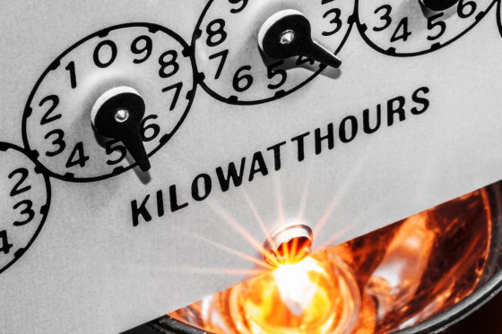 Macro close-up view of kilowatt hour electric meter register dials illuminated from below with light rays from energized electric light bulb