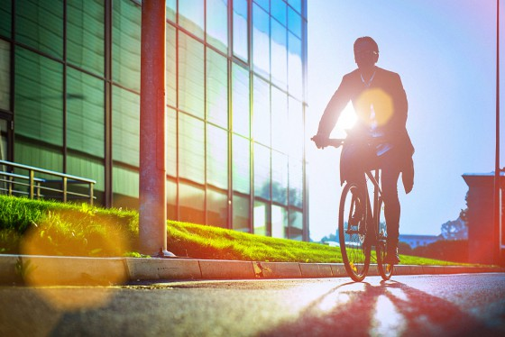 Handsome man, on the way to work, riding bicycle beside the modern office building. The man is casually dressed and wears eyeglasses and carries black briefcase hung on shoulder. Blurred motion, copy space has been left.
