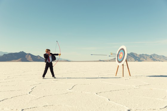 A young boy dressed in business suit, glasses and tie holds shoots a bow and arrow towards a target on the Bonneville Salt Flats in Utah. His business has found success and it mark for the future. He is smiling at the camera in front of blue skies.