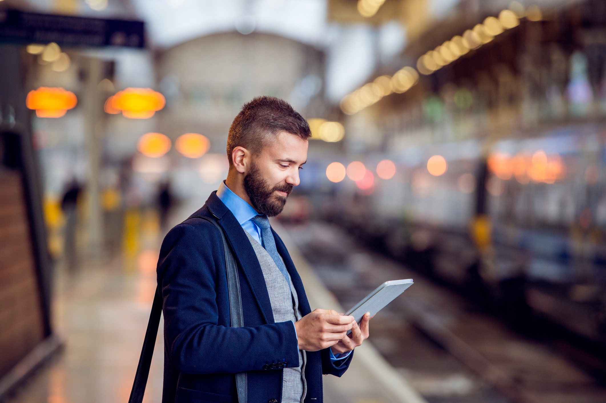 Hipster businessman with tablet, waiting at the train station platform