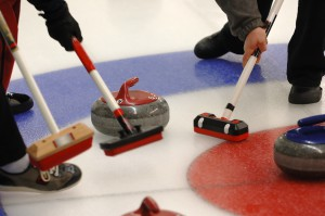Curling Action with sweepers and rock