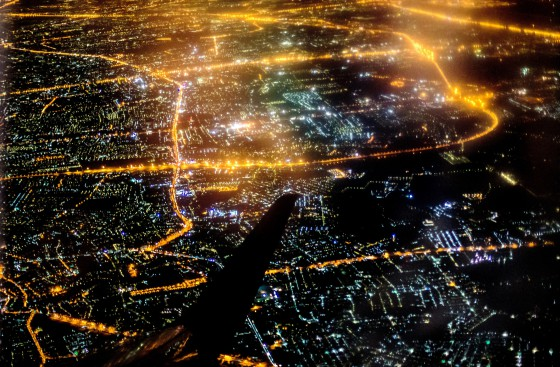 airplane wing over a city illuminated