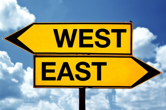 east or west, opposite signs. Two opposite signs against blue sky background.